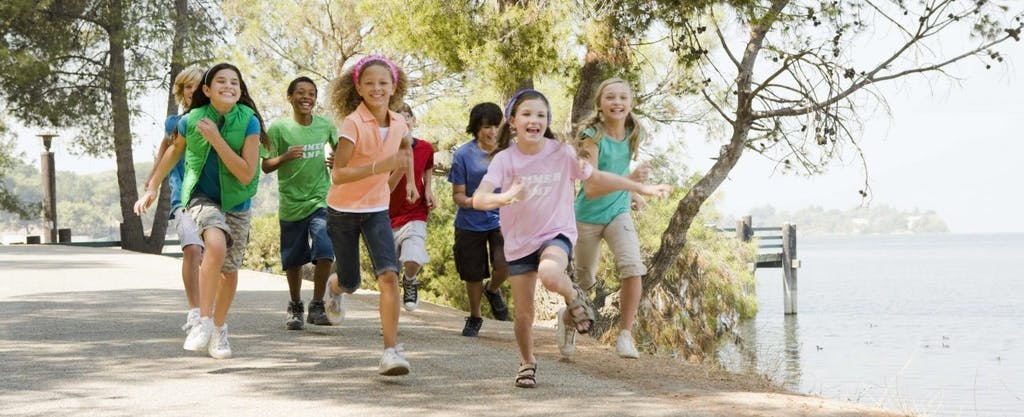 Children running and playing in summer camp. Their parents understand how FSAs work and the tax advantages they provide.