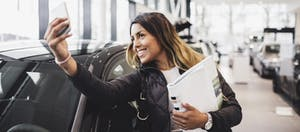 Smiling woman taking selfie with new car in showroom