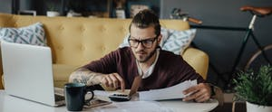 Young man in home interior going through household finances