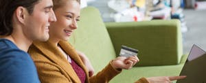 Happy young couple sitting together on sofa shopping online together using a laptop and credit card