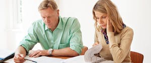 Mature woman and man calculating home finances at the table