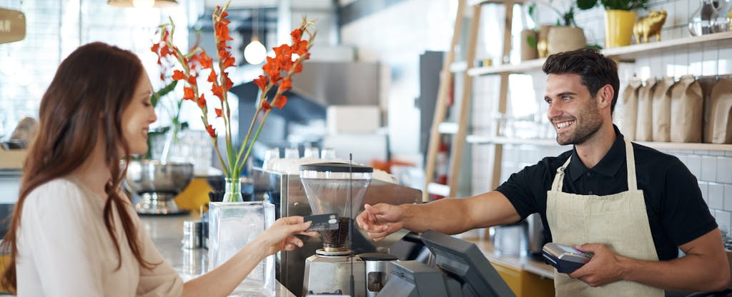 Male barista accepting a credit card for payment from a female customer in a light-filled coffee shop. Is it Visa? Mastercard?
