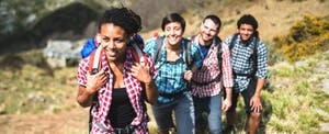 Group of young hikers walking up mountain
