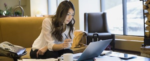 Businesswoman working at laptop in lobby