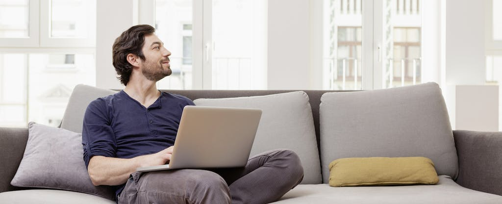Man sitting on couch using laptop, looking hopeful