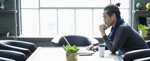Businessman using laptop in a modern office, looking serious