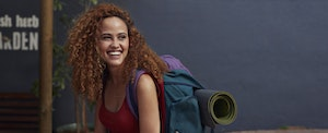 Young woman smiling, with travel backpack on