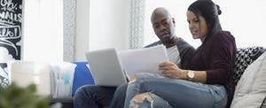 Couple with laptop discussing financial paperwork in living room