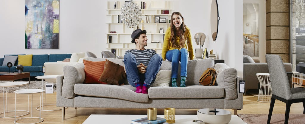 Couple in modern furniture store sitting on couch, laughing and wondering about the difference between their FICO score and credit score.