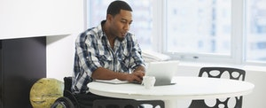 African-American businessman sitting at table and working on taxes for his startup.