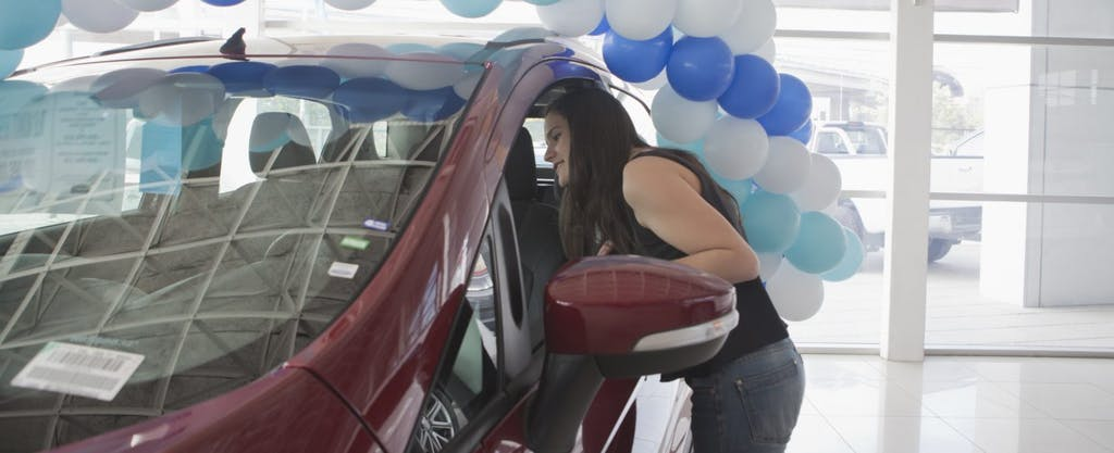 Young Hispanic woman looking at a car in a dealer showroom.