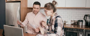 Couple in kitchen, looking at paperwork