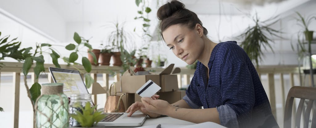 Female plant shop owner with credit card paying bills online at laptop in workshop