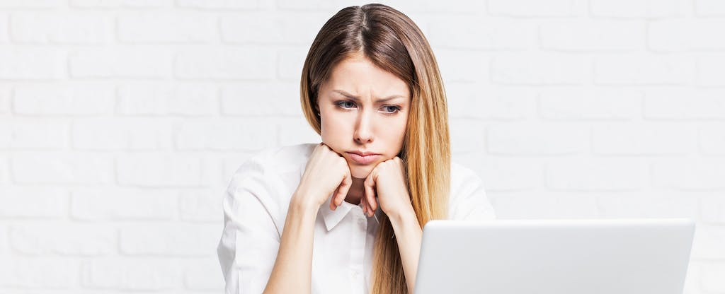 A stressed woman works on a laptop