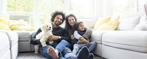 Family with dog sitting together in living room. Did they get their FICO scores free?