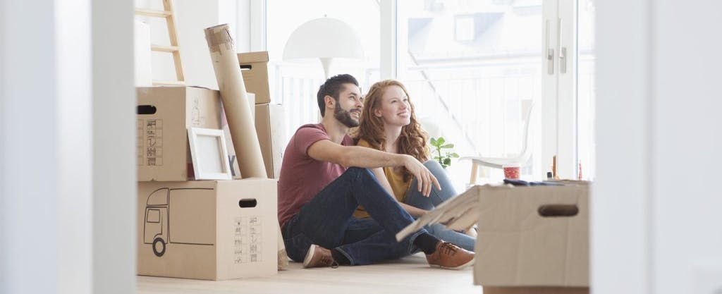 Happy young couple relaxing while unpacking after buying a home.