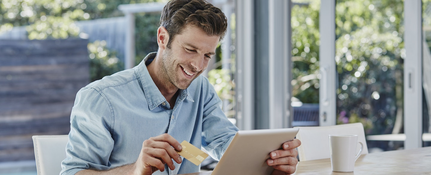 Smiling Male In A Sunny Room Looking At His Tablet With Credit Card