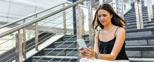 Young woman sitting on city steps, looking questioningly at her cellphone screen