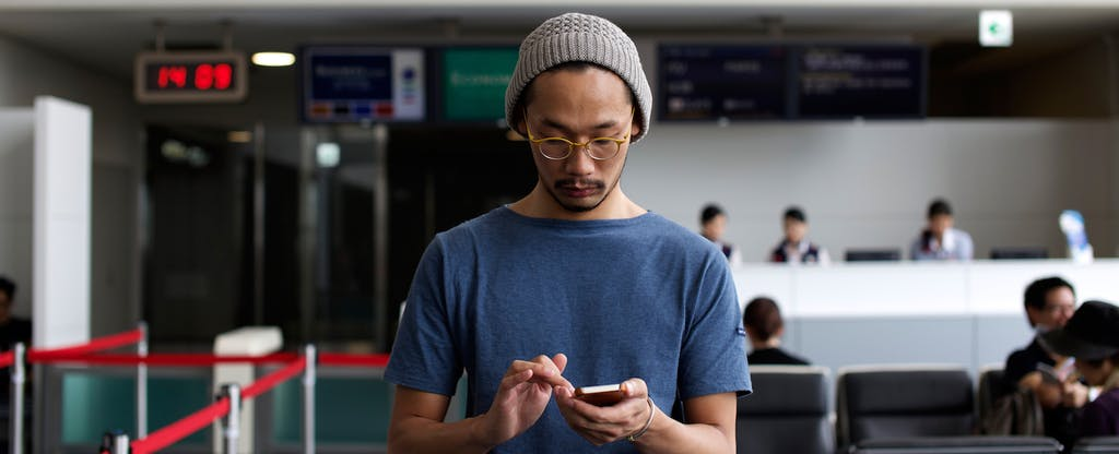 Man using smartphone at airport boarding gate.