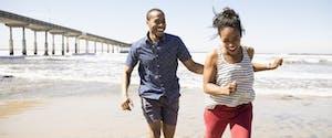 Playful couple run on sunny beach