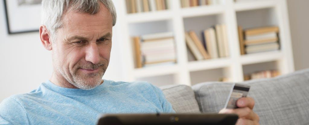 Man shops online with a digital tablet