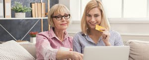 Adult woman and daughter shopping online with credit card and laptop.