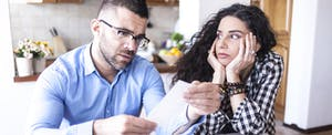 Worried couple looks at documents.