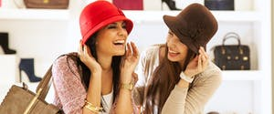 Two young women try on hats while shopping.