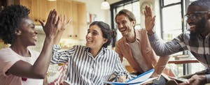 Creative business people high-fiving in meeting