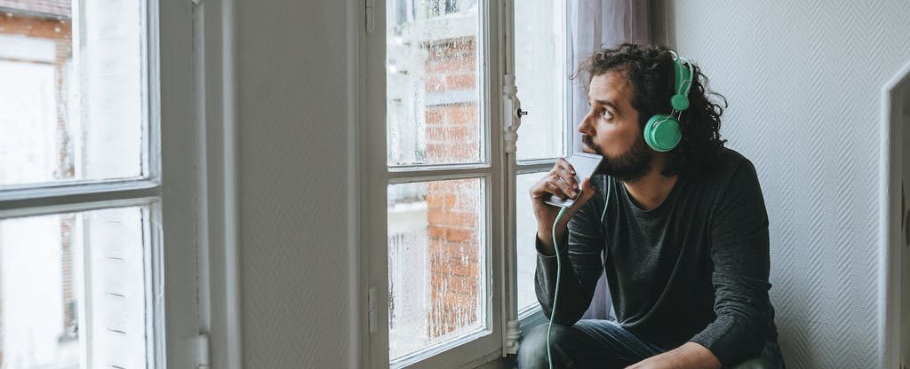 Man listening to music in his room looking out the window on rainy day.