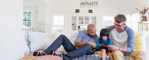 A male couple sits with their child on the living room sofa