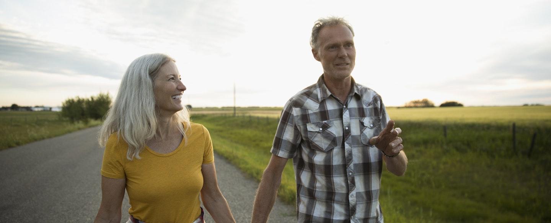 Couple Farmers Holding Hands Walking On Road Along Farm