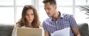 Worried couple researches how to get a personal loan with bad credit