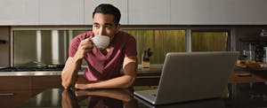 Young man thinking about a low interest personal loan over a cup of coffee