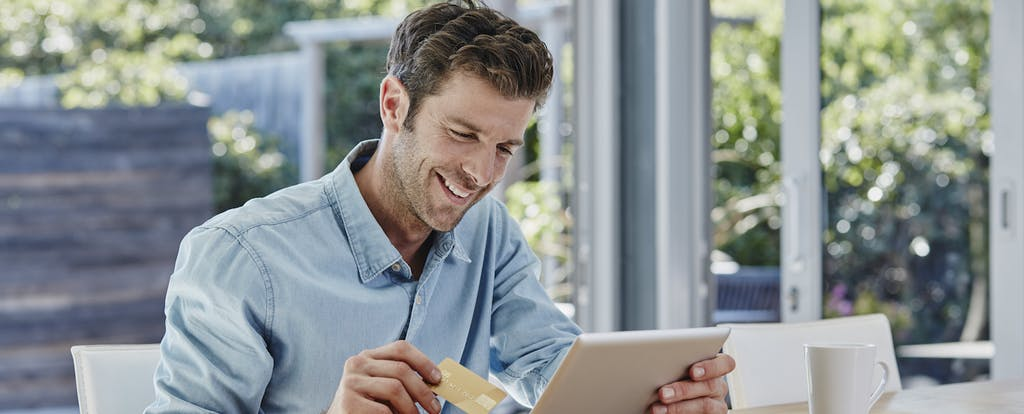 A blond man holds a credit card and a tablet and smiles about knowing how long a balance transfer will take.