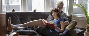 Young disabled woman sitting on couch with her boyfriend and reading about how tax reform affects ABLE accounts.