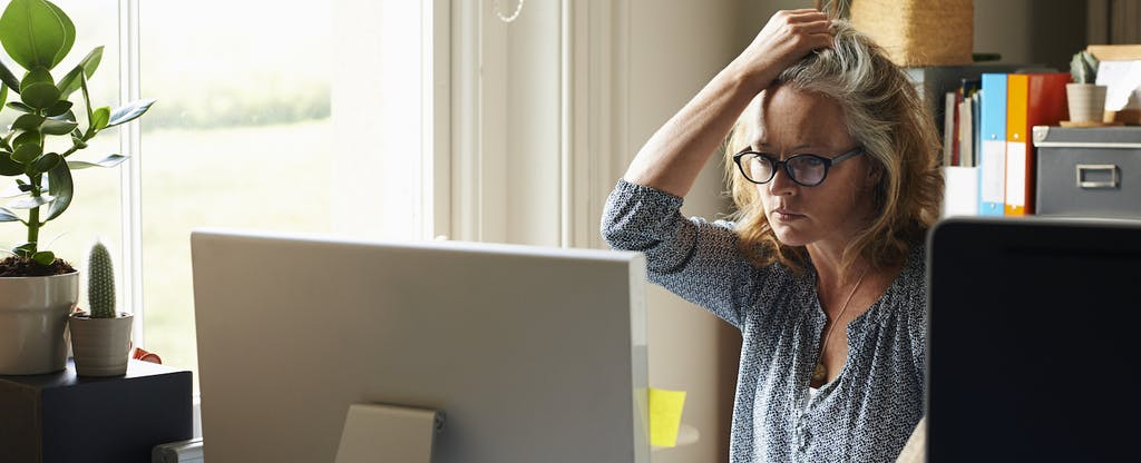 A stressed woman with a hand in her hair holding a credit card sits at a computer in home office