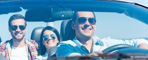 Group of happy people enjoying road trip in their convertible