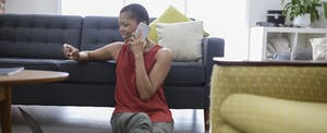 Mature woman with credit card talking on cell phone, using credit card at laptop on living room sofa