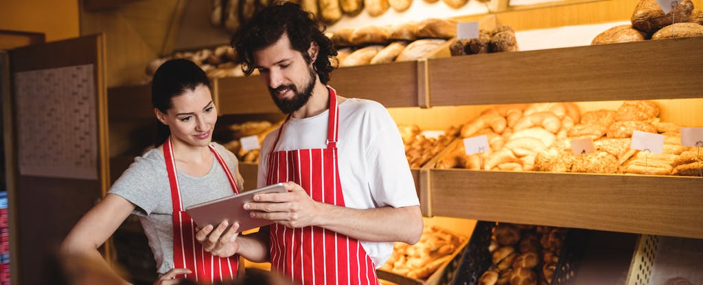 Couple using digital tablet in bakery shop.