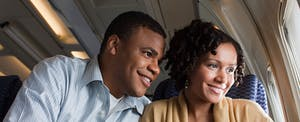 Smiling couple on an airplane looks out the window, happy that they maximized their Delta Air Line rewards