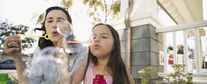 Grandmother and granddaughter blowing bubbles on summer porch