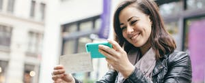 beautiful Caucasian adult woman sits in a New York city park, taking a picture of a check with her smart phone for a Remote Deposit Capture. She smiles, wearing modern stylish clothing with darker and black colors.