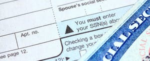 Close shot of the Social Security number field of a 1040 tax form, and the corner of a Social Security card.