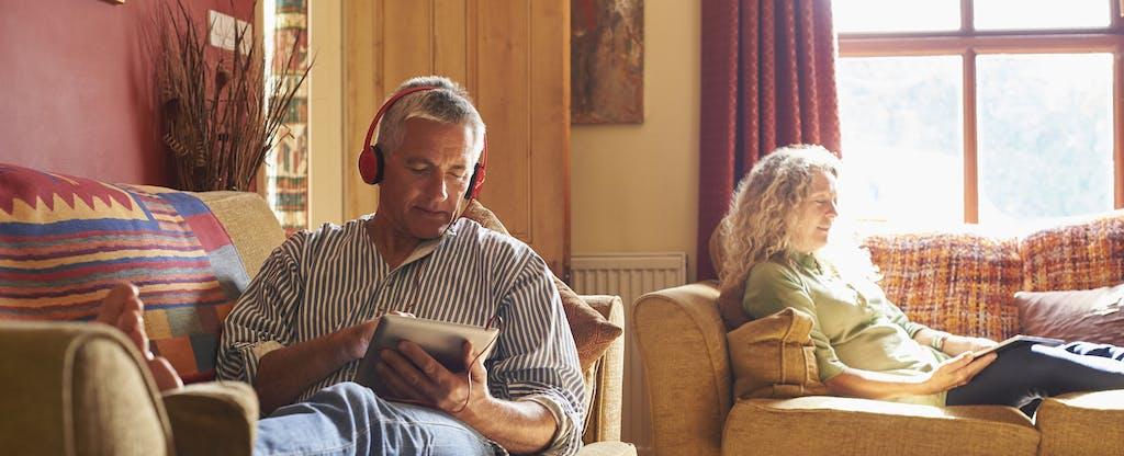 Older couple sitting on sofas using digital tablets