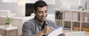 A man opens mail in his home office, hoping to hear back about a small personal loan.