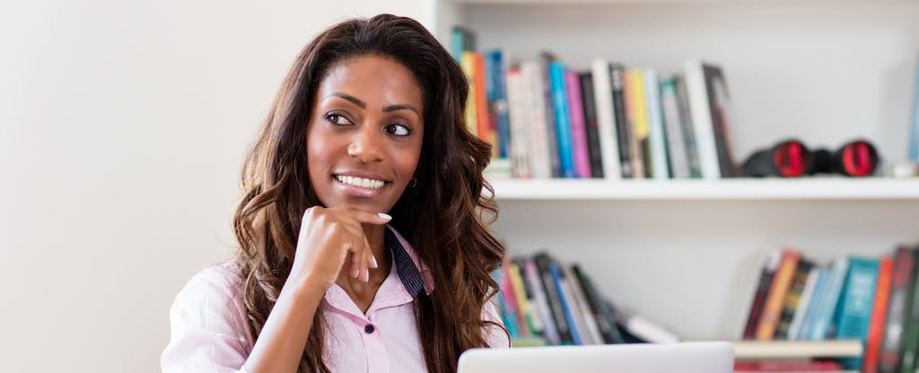 Musing African American woman at computer with bookshelf