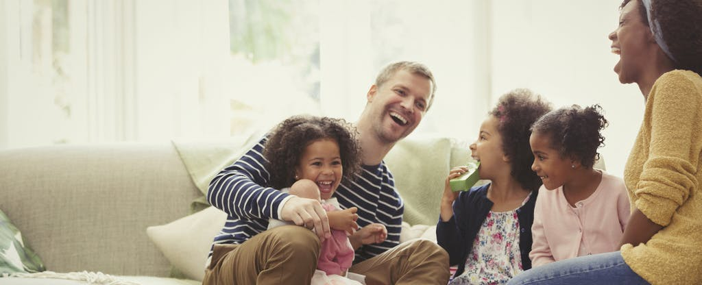 Young family laughing on sofa