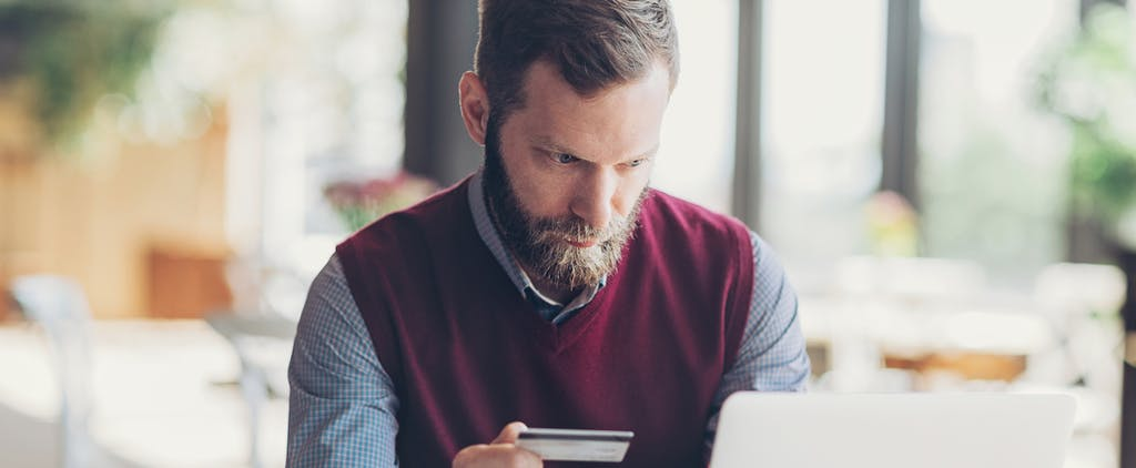 Man with beard holding a credit card and using laptop in cafe