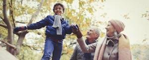 Grandparents walking grandson in autumn park